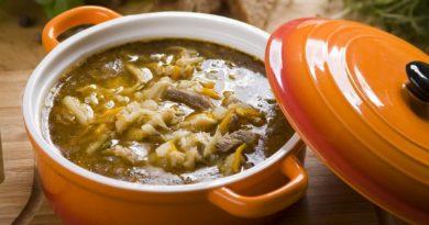 Польский суп из говяжьих рубцов. Чтобы избавиться от характерного запаха, рубцы предварительно хорошо промывают и отваривают в бульоне с кореньями. Иногда на предварительную обработку может уйти до 5 часов, но результат оправдывает затраченные усилия, так как вкус супа насыщенный и яркий. По консистенции суп получается достаточно густым, представляя собой нечто среднее между первым и тушёным вторым блюдом. На 6 порций Время приготовления: 4,5 часа 400 г говяжьих костей 4 л воды 1 кг говяжьего рубца 1 крупная луковица 2 крупные моркови 150–200 г корня сельдерея 2 ст. л. сливочного масла 1 ст. л. пшеничной муки 0,5 ч. л. тёртого мускатного ореха 0,5 ч. л. молотого имбиря 0,5 ч. л. сушёного майорана 100 г твёрдого сыра соль и перец по вкусу Калорийность: 63 ккал • Кости промыть, залить холодной водой. Поместить на огонь, довести до кипения, затем уменьшить огонь до слабого, варить в течение 2 часов. Бульон процедить. • Рубец промыть под проточной водой, положить в отдельную кастрюлю, залить водой, довести до кипения, слить воду. Ещё раз хорошо промыть. • Залить рубец половиной костного бульона, варить 3–4 часа на слабом огне. Лук и морковь очистить. • За 30 минут до готовности рубца положить в кастрюлю 1 морковь и 0,5 луковицы. Варить до готовности рубца, затем извлечь его и нарезать тонкими полосками, бульон вылить. • Оставшийся лук нарезать полукольцами, морковь – тонкими брусочками. Сельдерей очистить, нарезать соломкой. Обжарить овощи в 1 ст. ложке сливочного масла. • В оставшемся масле обжарить муку до золотистого цвета. Влить вторую половину бульона, положить рубец и обжаренные овощи. Посолить, добавить специи. • Сыр натереть. Суп разлить по тарелкам, посыпать тёртым сыром, подать к столу.